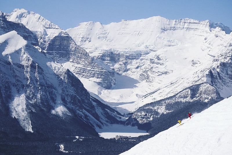 Two skiers racing in Lake Louise with perfect snow and beautiful views