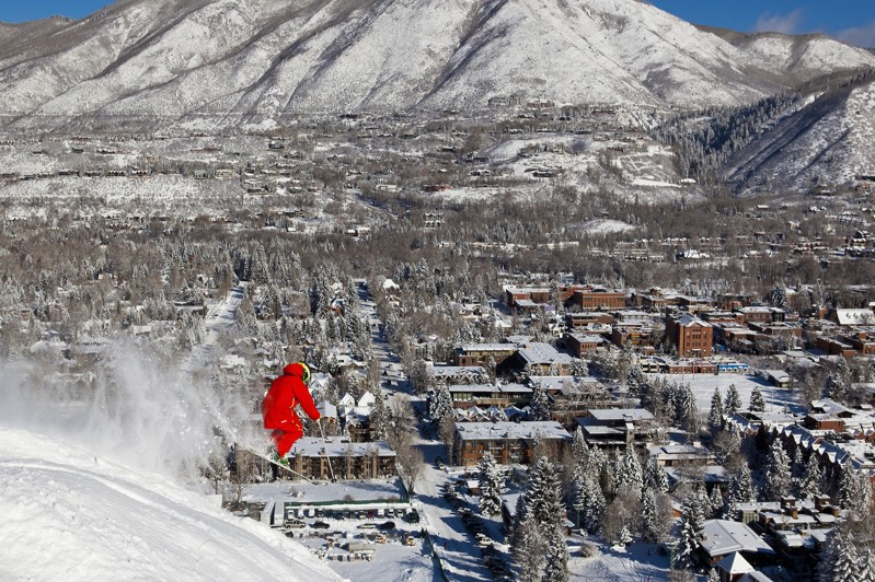 Skier leaps with Aspen town in the background