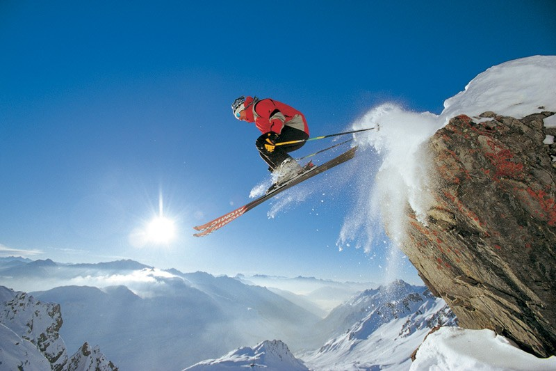 A skier performs a daring jump off a rock in St Anton, Austria