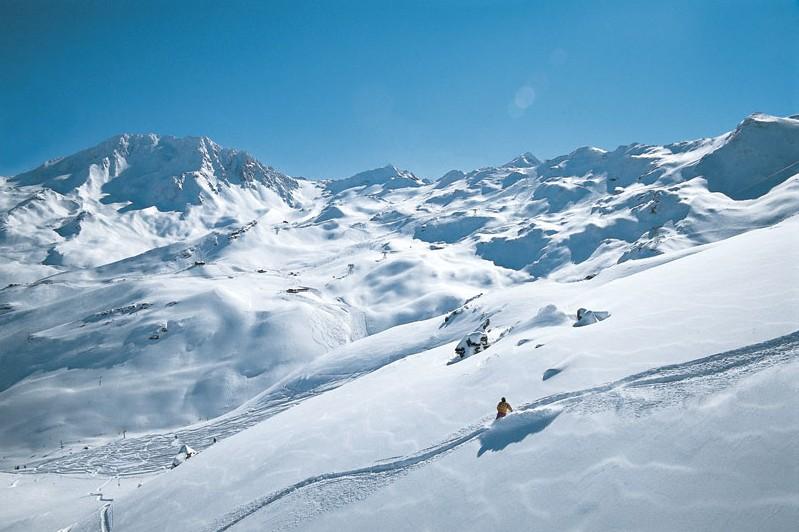 A solo skier enjoys fresh powder in Val Thorens