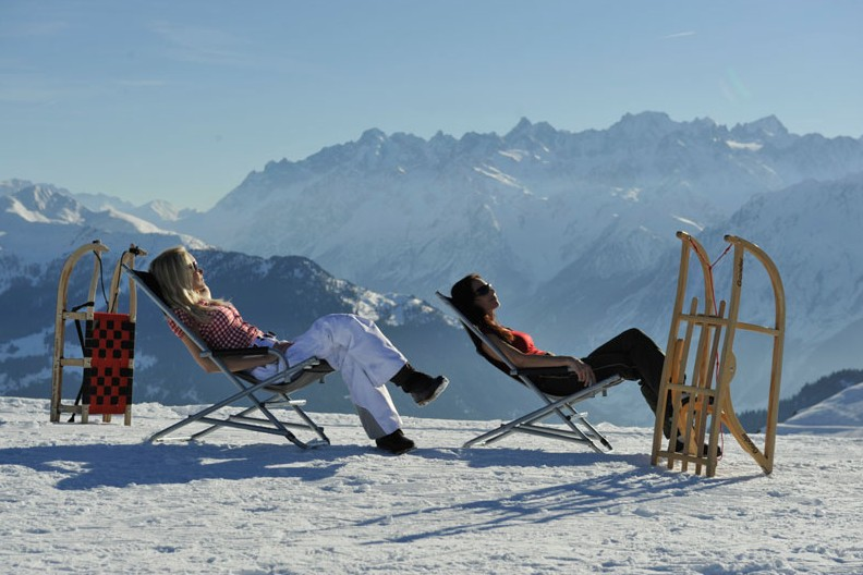 Skiers sunbathing at the top of the mountains in Verbier