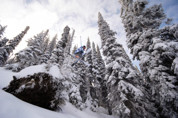 Skier jumps from rock surrounded by trees in Big White