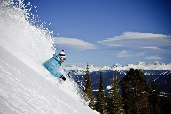 Breckenridge skier skis powder snow on a sunny day