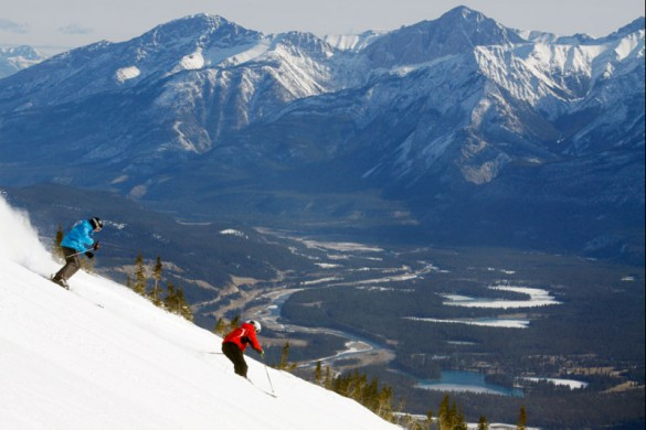 Two skiers riding steeps with mountain backdrop in Jasper