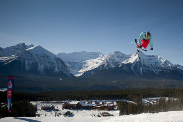 Skier pulling a trick with mountains in the background