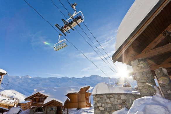 A chair lift passes over snow covered chalets in Val Thorens
