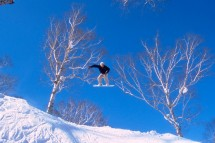 Snowboarder surrounded by blue sky jumps in Niseko, Japan