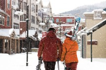 A couple enjoy a snowy walk home after a days skiing in Park City