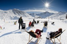 A group of friends relaxing under the sun in deckchairs in Tignes