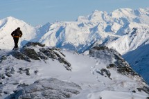 A hiker stops to admire the view from the top of the mountain in Verbier